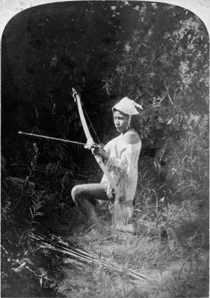 """thebigkelu: """"A young Native American (Paiute) woman, Kómohoats, kneels on the ground holding a bow and arrow, The Meadows, southwestern Nevada - Hillers - 1874 """""""