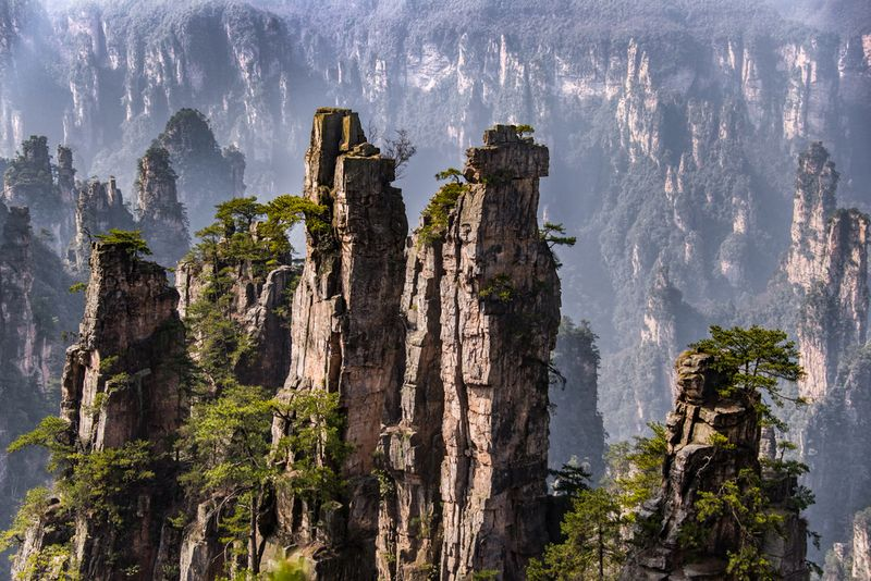 """Located in China's southern Hunan Province, theZhangjiajie National Forest Park is a surreal expanse of stone spires that have greenery growing in every crack and crevice. The forest floor is carpeted with trees and burbling streams that run in between the valleys and gorges among the sandstone columns. This landscape was the inspiration for portions of the planet Pandora from James Cameron's Avatar. One of thespires in the park has even been renamed the """"Avatar Hallelujah Mountain."""""""