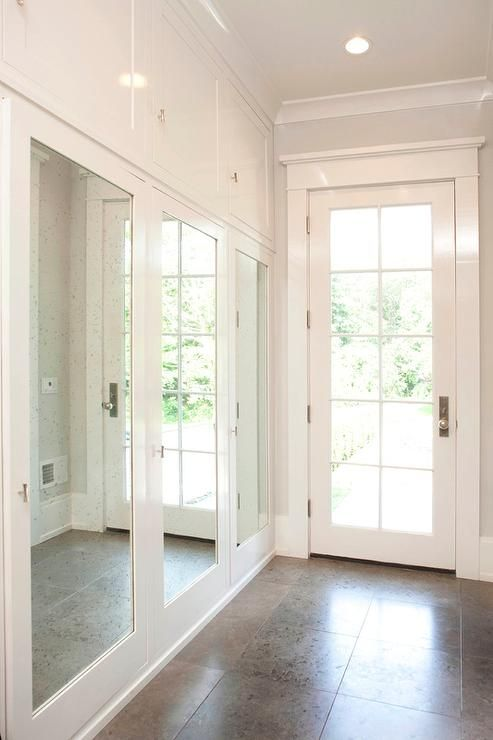Long Mudroom Features A Row Of Closets Finished With Mirrored Doors