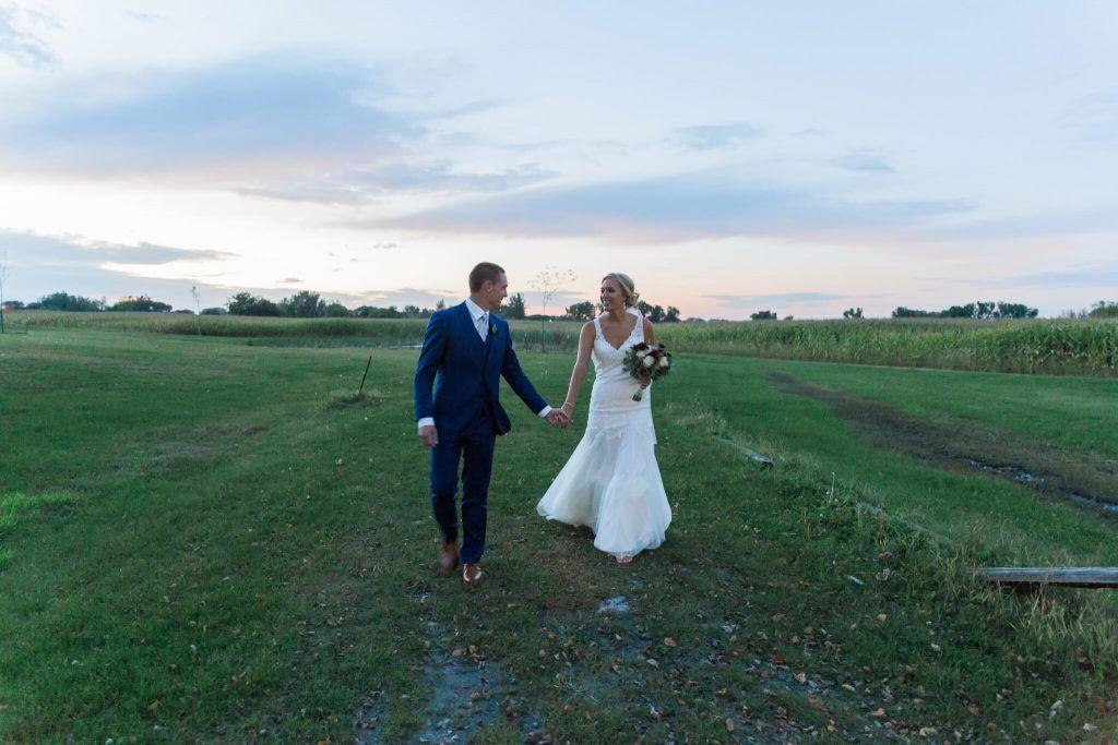 bride and groom walking in vineyard in central minnesota ...