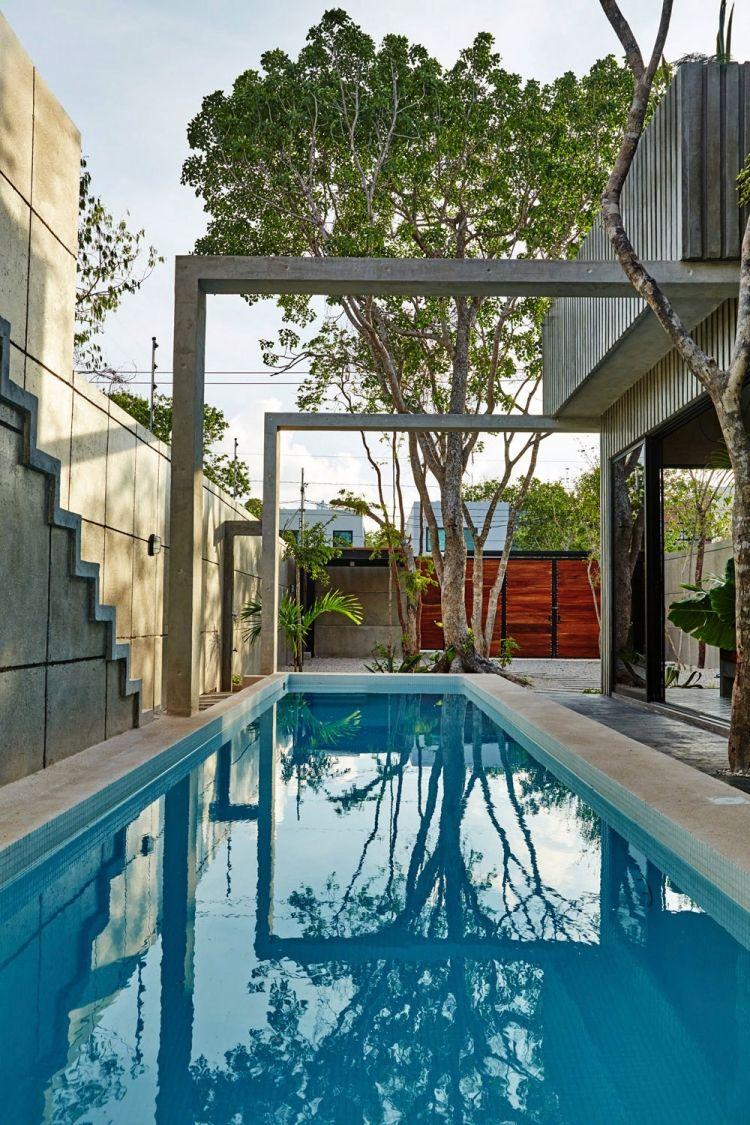 das Haus wirft Schatten teilweise auf rechteckigen luxuriösen Pools ...