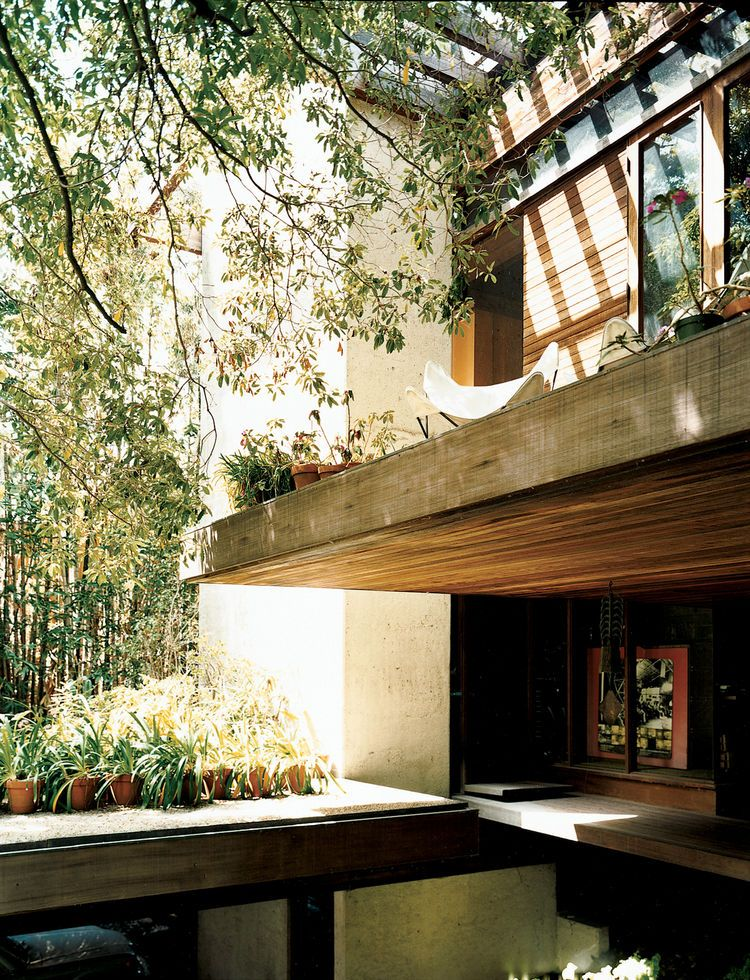 The front door is tucked under a cantilevered terrace.