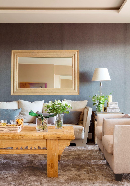 salón con pared y cojines gris azulado, mesa de centro de madera de