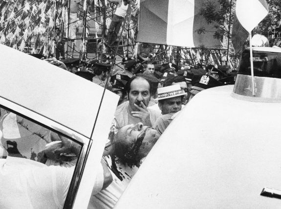 The body of Joseph Colombo is put in a police vehicle minutes after being shot by a non-gangster during a rally of the Italian American Coalition at Columbus Circle.
