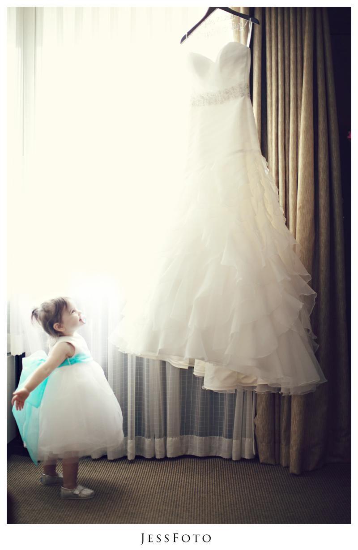 Flower girl looking at wedding dress dress on hanger july wedding