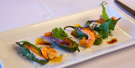 Savor an appetizer of Roasted Jalapenos with goat cheese-Laughing Bird shrimp, and house-cured bacon.
