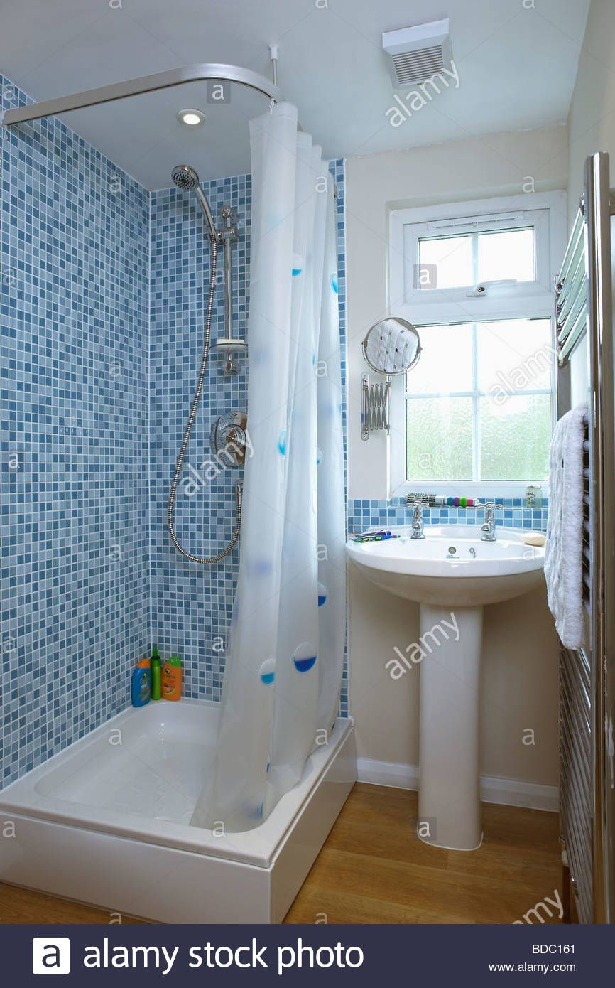 Blue mosaic wall tiles above bath with white shower curtain in ...