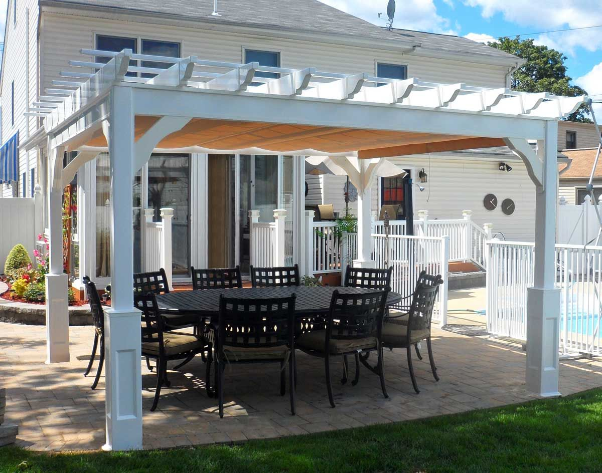 This vinyl Pergola has been enhanced with a fabric roofing material for  light blockage and easily