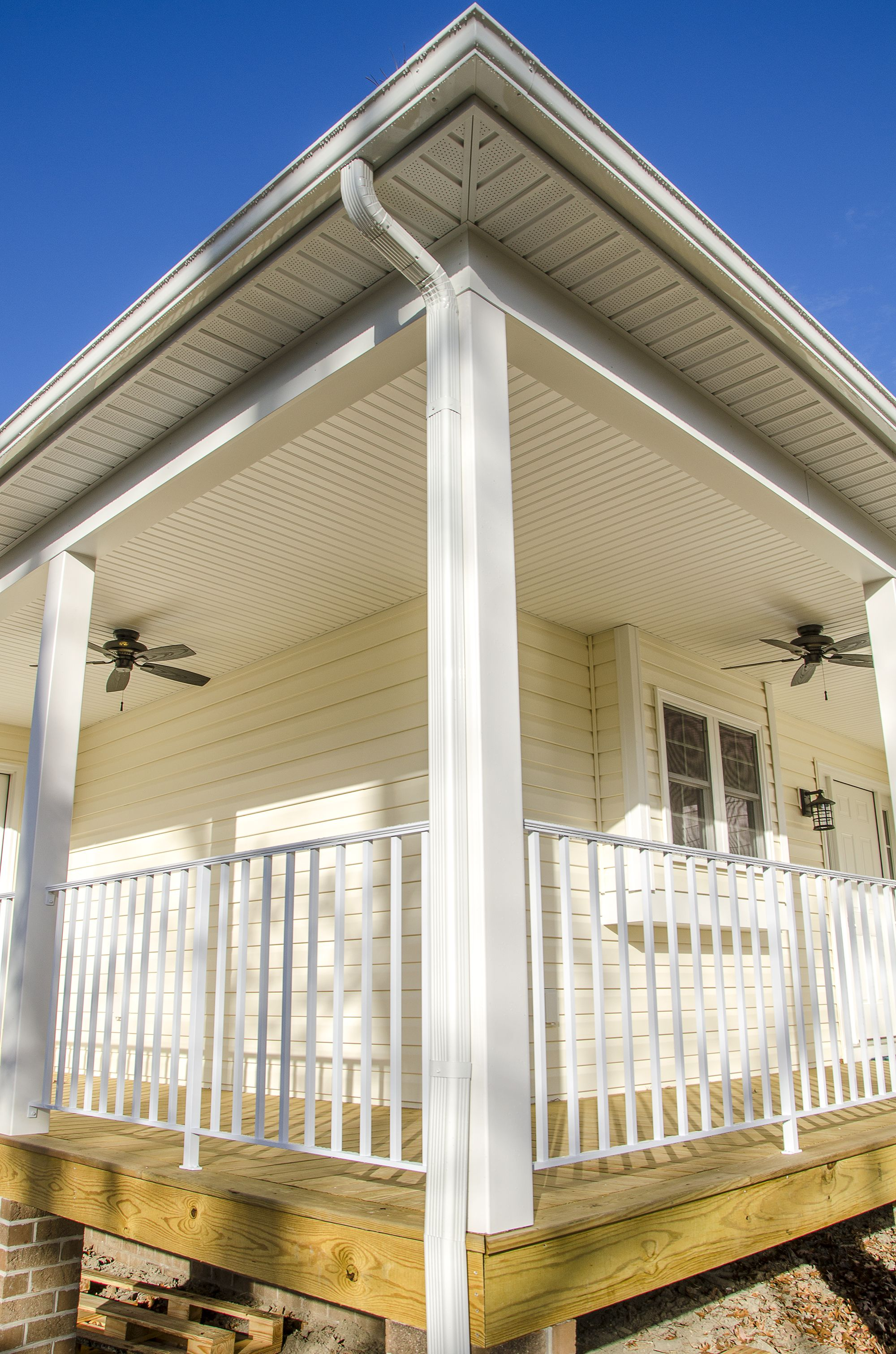 Beautiful wrap around porch with yellow vinyl siding and two exterior ceiling fans ©Balducci Exteriors