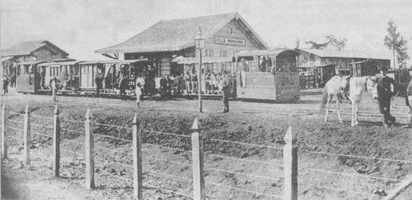 Estação Vila Mariana do Tramway de Santo Amaro. Os trilhos estavam no leito da rua Domingos de Moraes. No local depois foi construída uma garagem de bondes da Light e hoje é um terreno cercado com o emblema do Metrô. Fica em frente à atual rua Sud Mennucci. Autor desconhecido. Provavelmente anos 1890