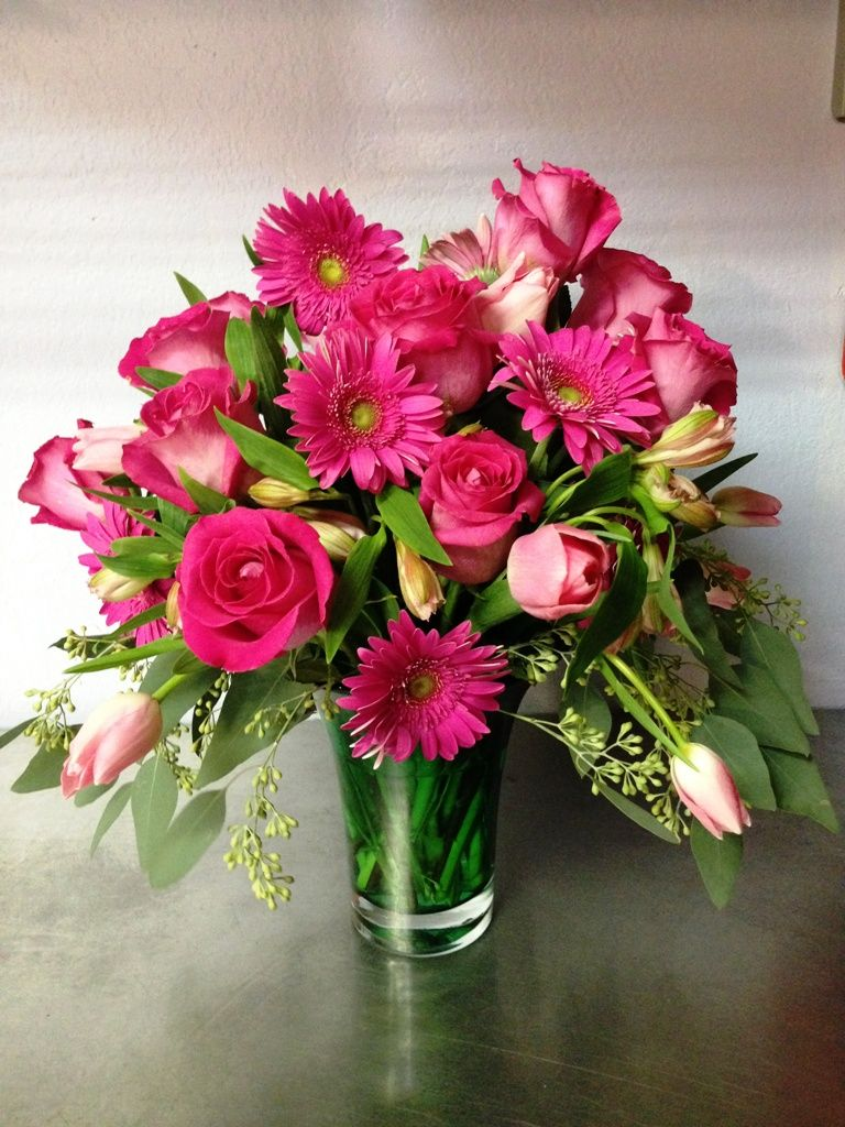 Hot pink roses and gerber daisies mix with pink tulips and seeded hot pink roses and gerber daisies mix with pink tulips and seeded eucalyptus in a green reviewsmspy