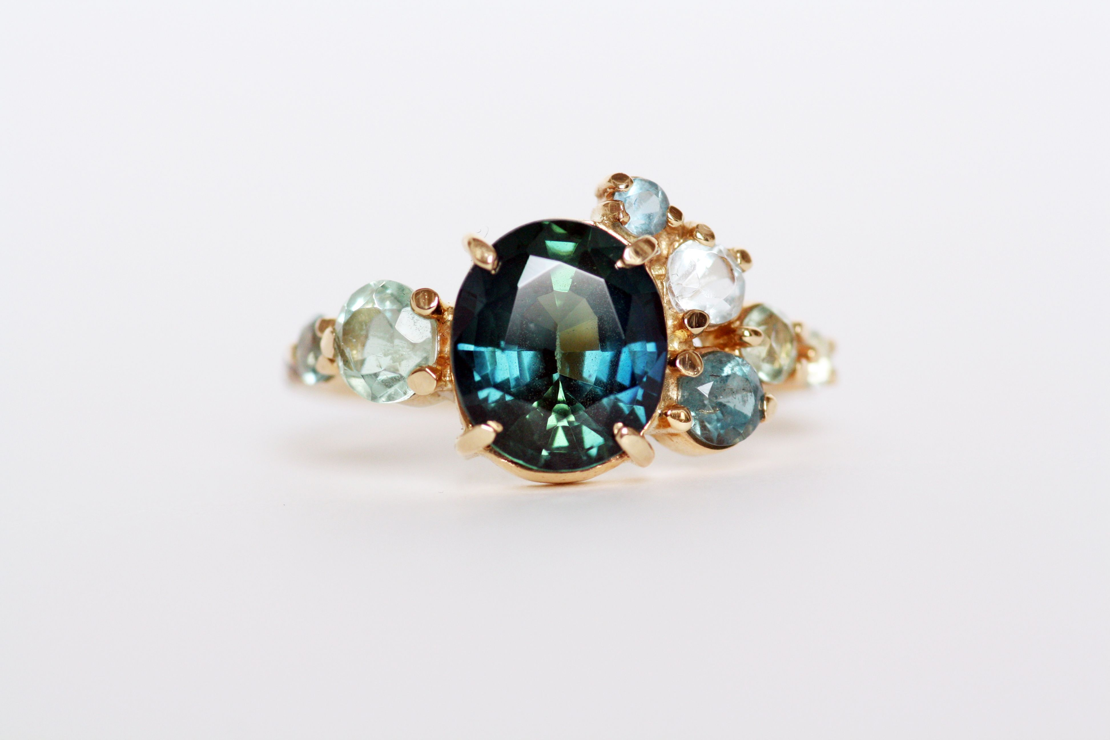 Arch cluster ring featuring a 3.00 ct. Australian blue green bicolor sapphire. Flanked by aquamarine. Set in 14K yellow gold.