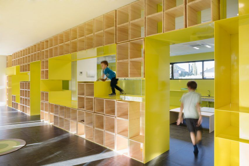Walls with integrated furniture and yellow nooks encourage play in