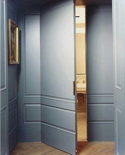 puerta con bisagras invisibles integrada en una pared de paneles de madera