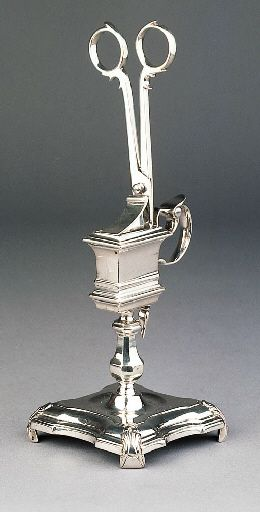 A Dutch silver candle snuffer & stand - Maker's mark on stand of Bernardus Blencke, Groningen, c.1741. Stand on incurved shaped square pedestal raised on four foliate scroll feet, with reeded borders & panelled octagonal baluster shaped column, holder rectangular with moulded base & rim, triple-curved handle & plain curved thumbpiece, snuffers of typical scissor form with shaped rim & reeded baluster terminal, engraved with a coat-of-arms within plumed mantling 22cm. high