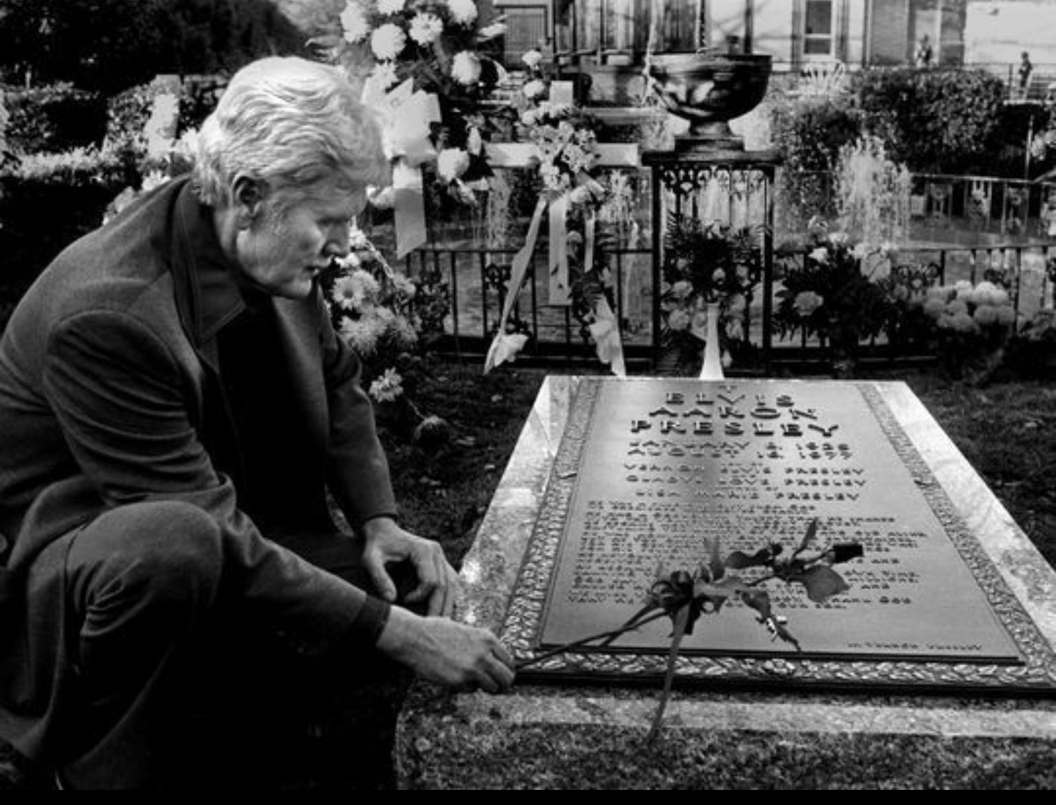 Vernon Presley, Elvis' father, places a rose on his son's ...