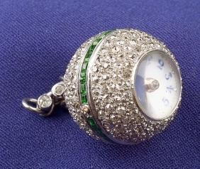 Art Deco Platinum Diamond and Demantoid Garnet Ball Watch, the white enamel dial with red and blue Arabic numeral indicators, pave-set with old mine-cut diamonds and channel-set with step-cut garnets, enclosing gilt jeweled movement, bezel-set diamond bail.