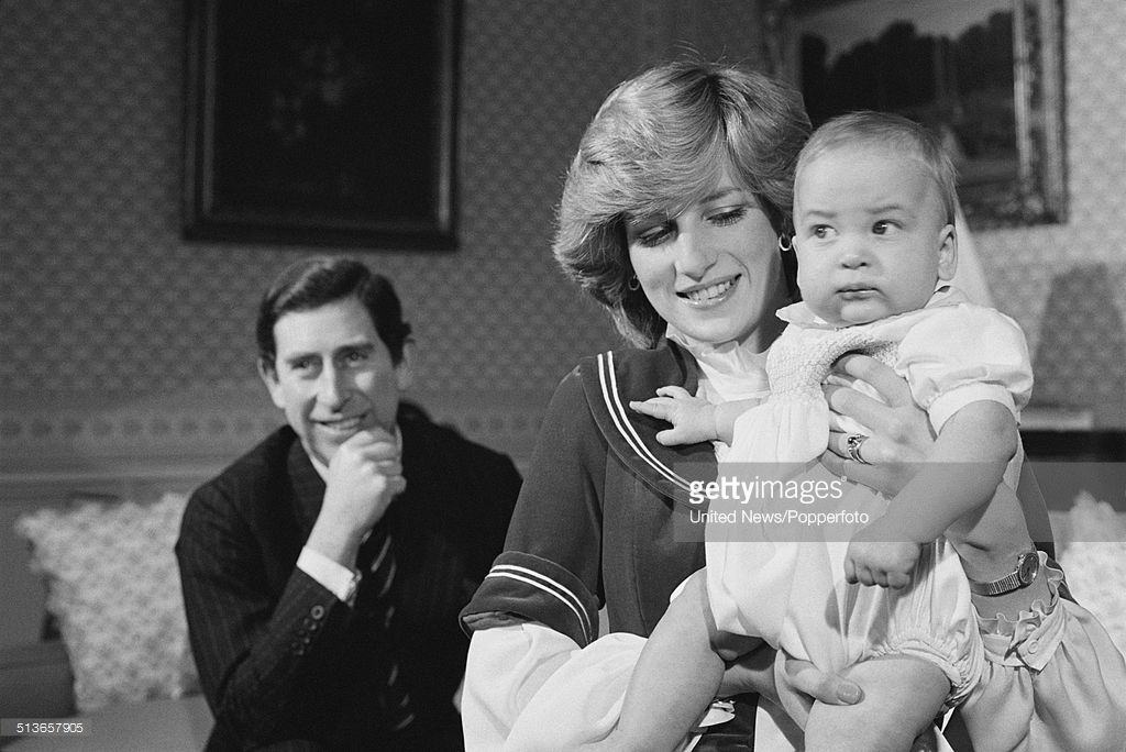 Prince Charles looks on as Diana, Princess of Wales holds their baby son, Prince William at Kensington Palace in London on 22nd December 1982.