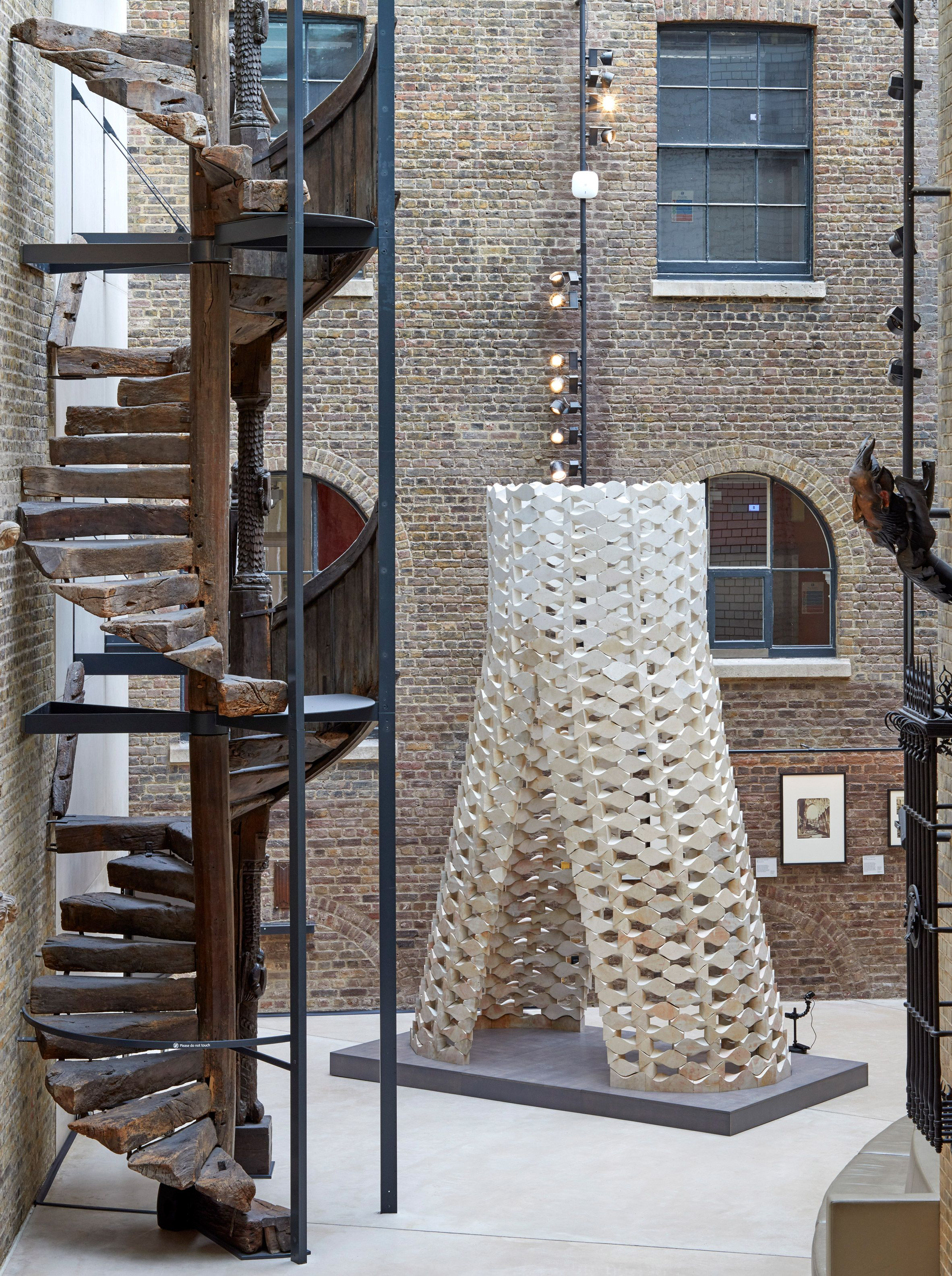 Robots cut the curvy blocks that make up this stone tower, which ...