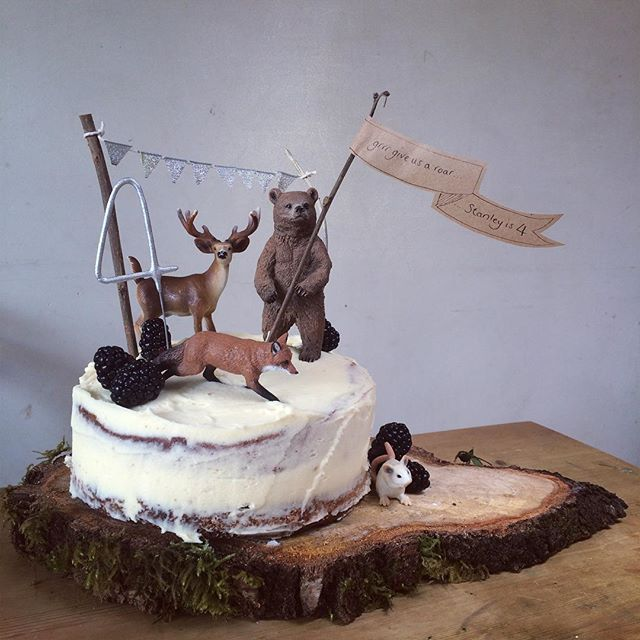 forest birthday cake on wood round (board) w/ plastic animals (bear, deer, fox, bunny) & kraft banner
