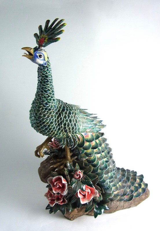 A large Chinese stoneware model of a peacock. A large Chinese stoneware model of a peacock. 20th century. Finely modelled with colourful turquoise glazed plumage, a detachable head crest and depicted perching on a rocky outcrop incised with Archaistic characters and seal marks to one side and encrusted with roses and foliage. 17.9 in (45.5 cm) height, 13.4 in (34 cm) length.