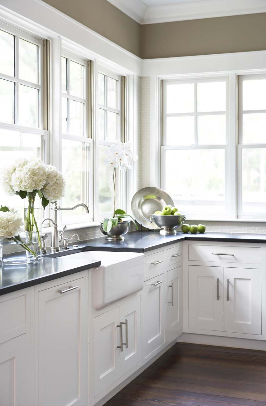 White Farmhouse Sink With White Custom Cabinets And Black Granite
