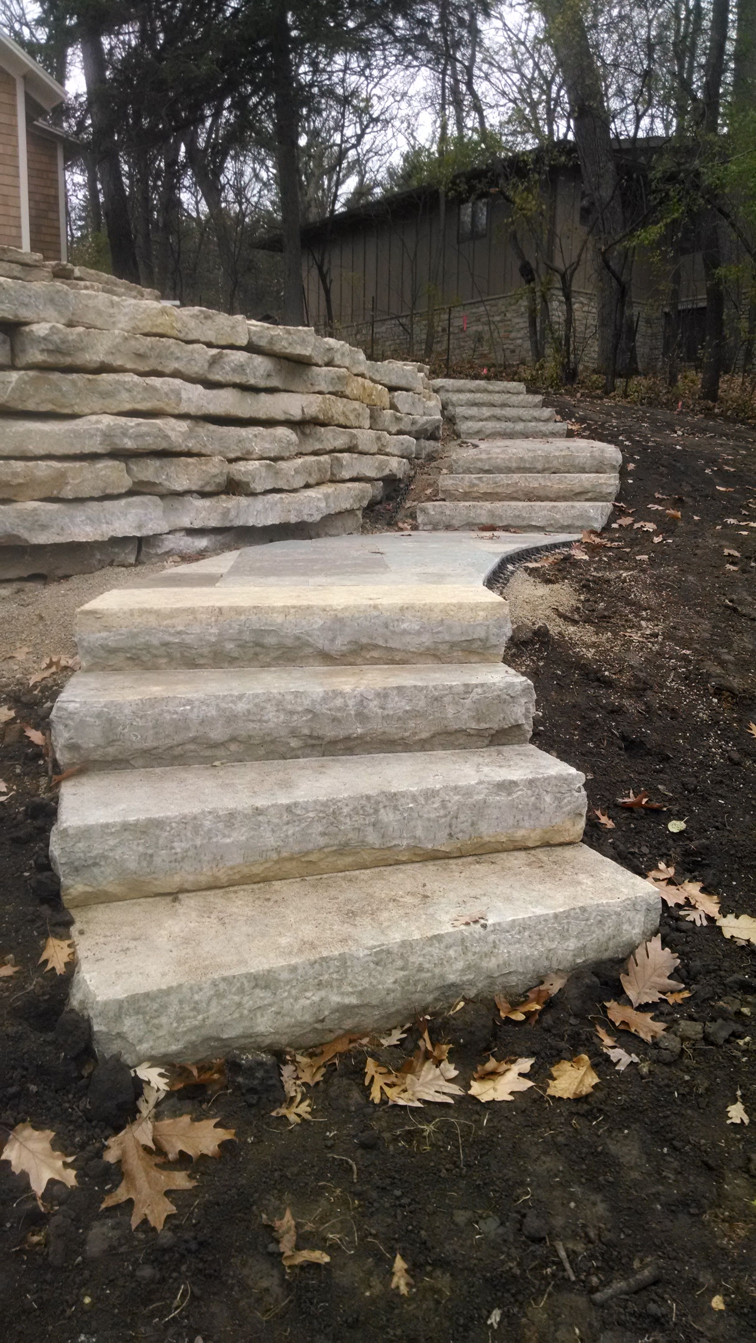 The natural stone steps of a stairway garden feature climb a small - Natural Stone Steps With Outcropping Walls By Outdoor Impact Landscape And Shoreline Services