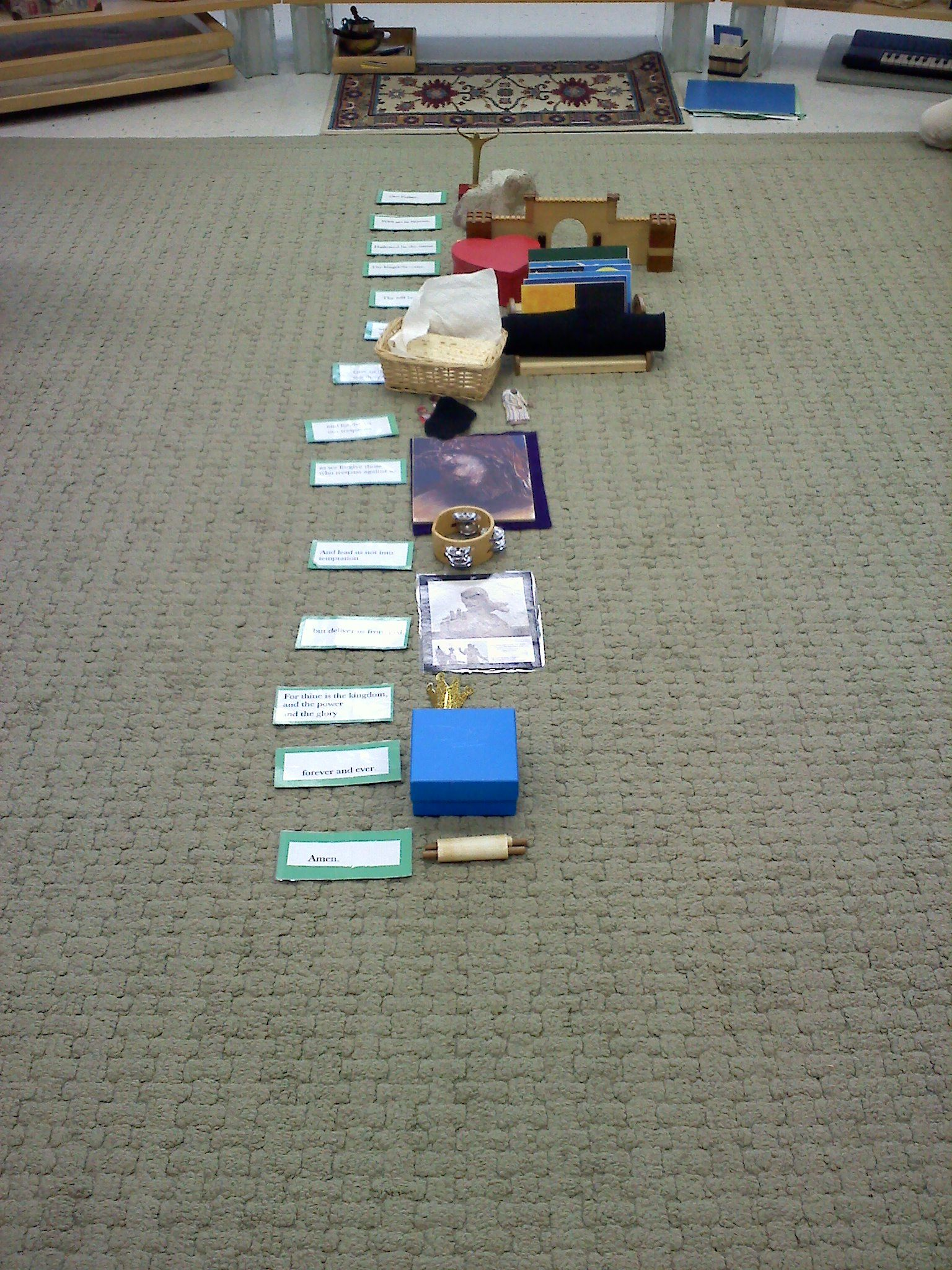 """Teaching the Lord's Prayer phrase by phrase (cards on the left) with objects from Godly Play(TM) stories chosen by the children to """"illustrate"""" it."""
