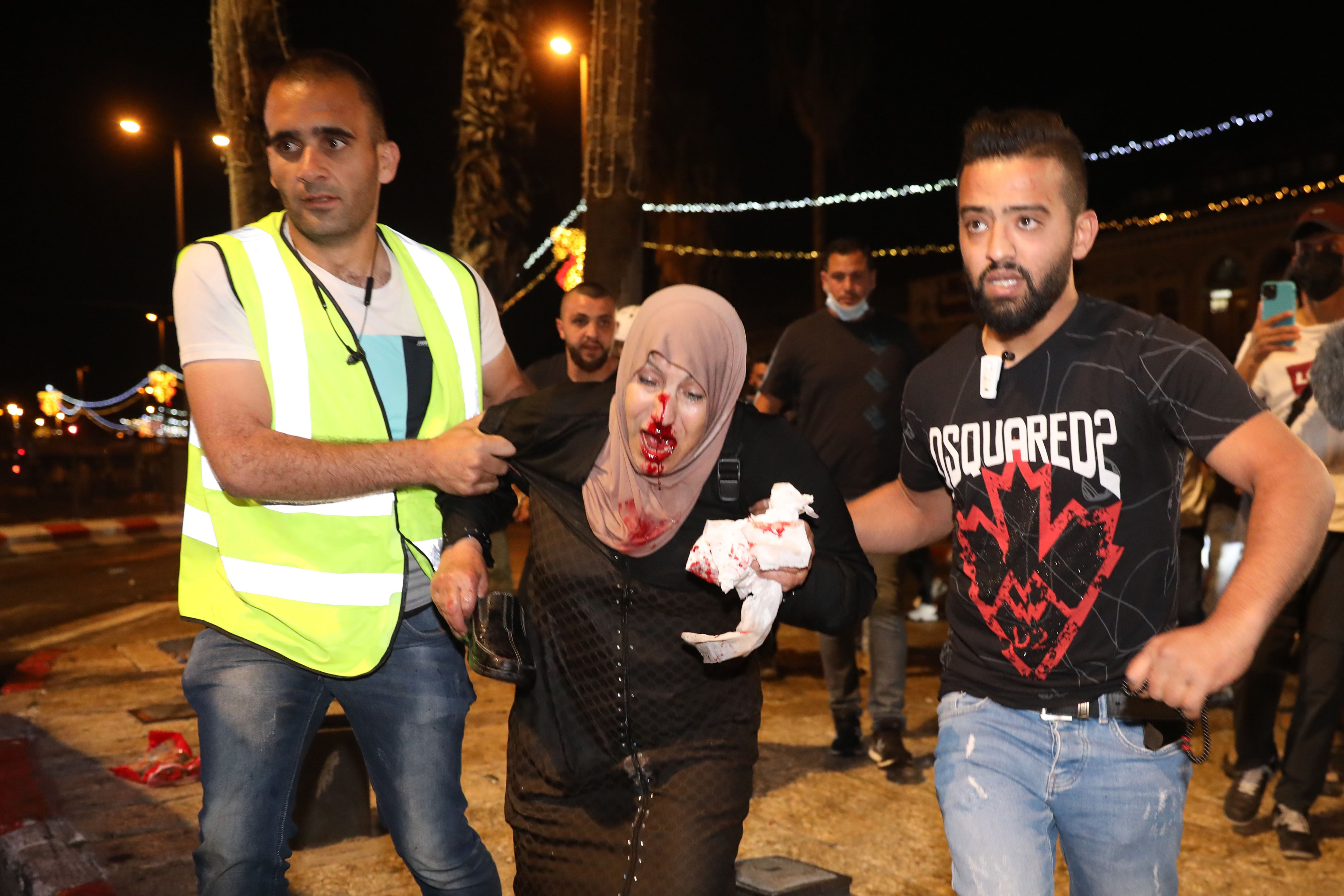 People help an injured Palestinian woman during a protest at the Damascus Gate [Abir Sultan/EPA]   Al Aqsa Mosque attacked
