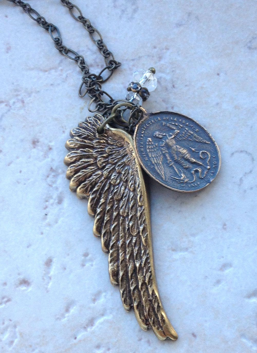 The st michael angel wing necklace features a lovely detailed a detailed bronze wing dangles alongside a delicate st michael the archangel medal with a miraculous medal on the reverse faceted crystals and rondelles aloadofball Image collections