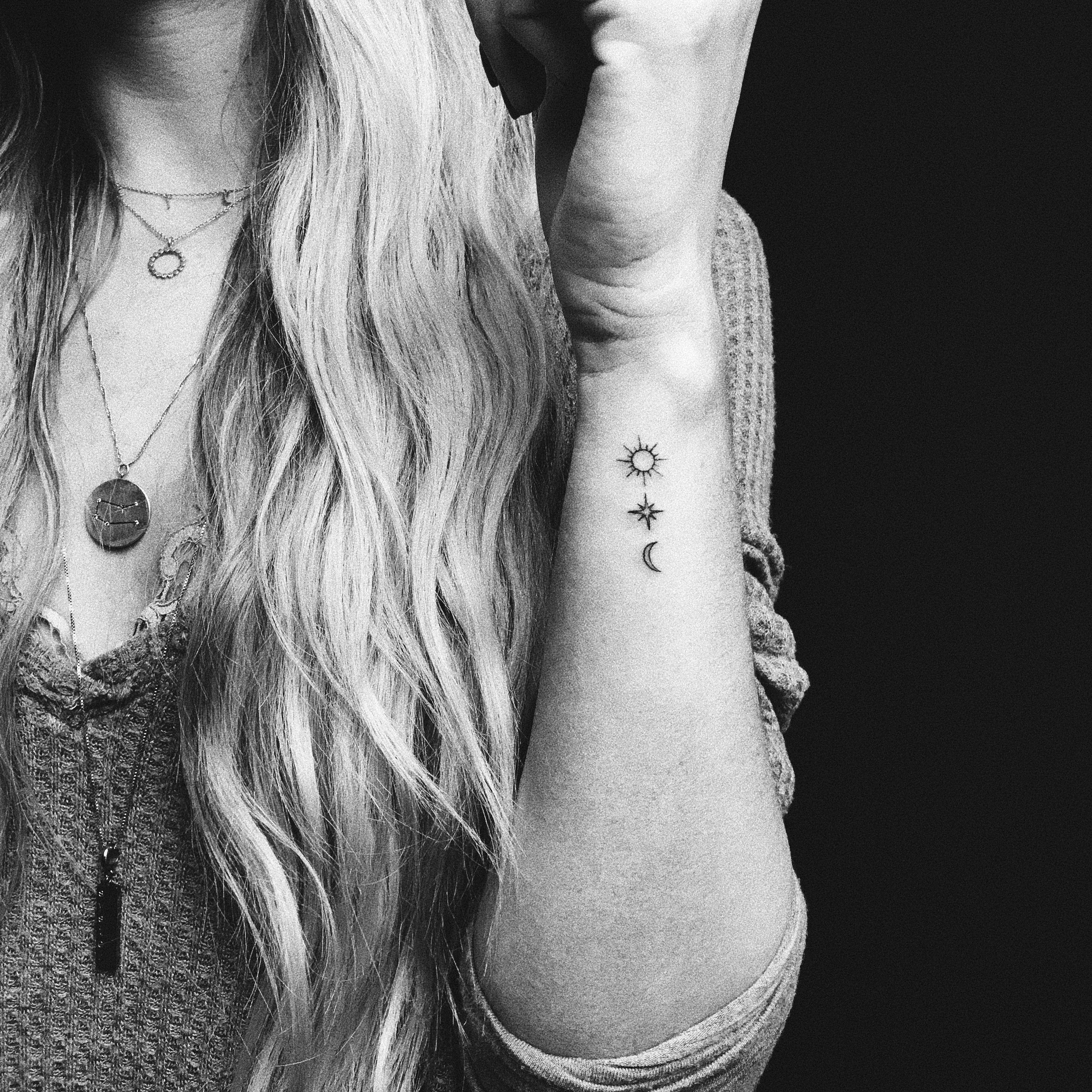 Dainty sun moon and star minimalistic fine line tattoo.