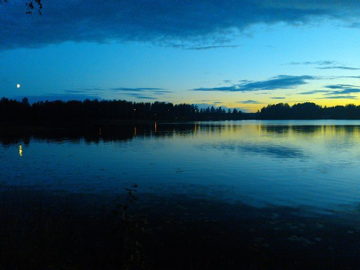 The setting sun and the rising moon in the same image. Iisalmi Finland by Janne Tikkanen