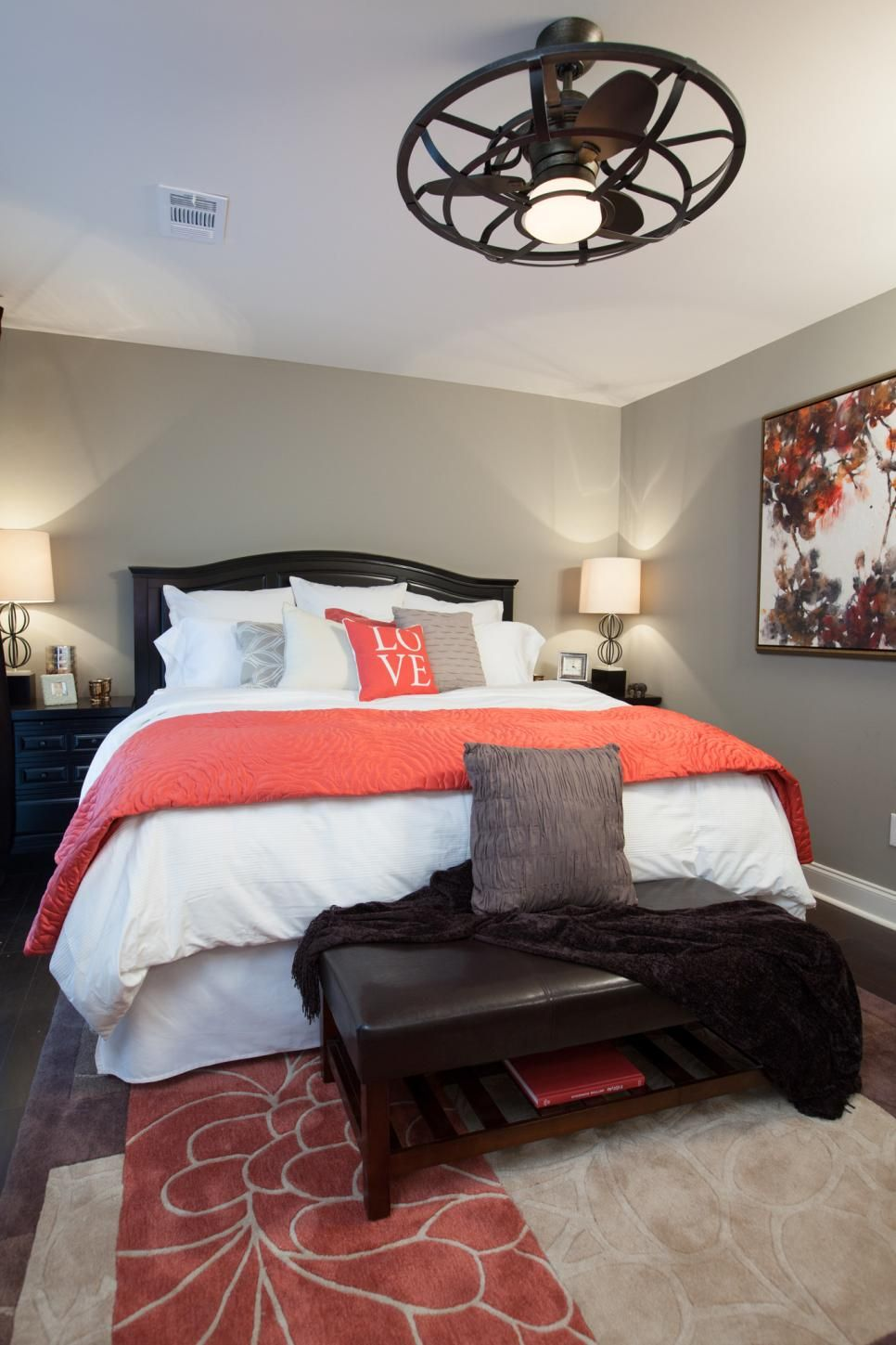 MASTER BEDROOM, AFTER: This newly renovated bedroom is warm and inviting with brand new hardwood floors, unique ceiling fan and pops of coral through the room. #graybedroomwithpopofcolor