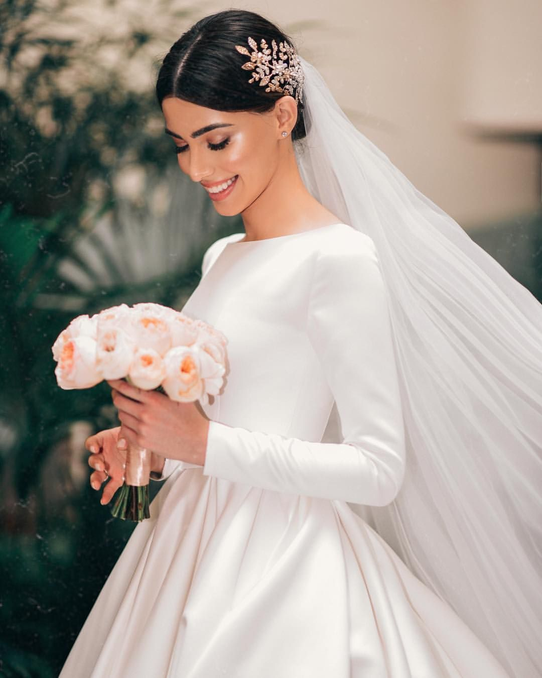 A Beautiful Bride Wearing A Simple But Elegant Long Sleeved