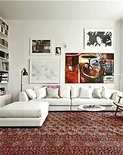 Room Sized Persian Rug And Colorful Art With Neutral Sofa And Walls