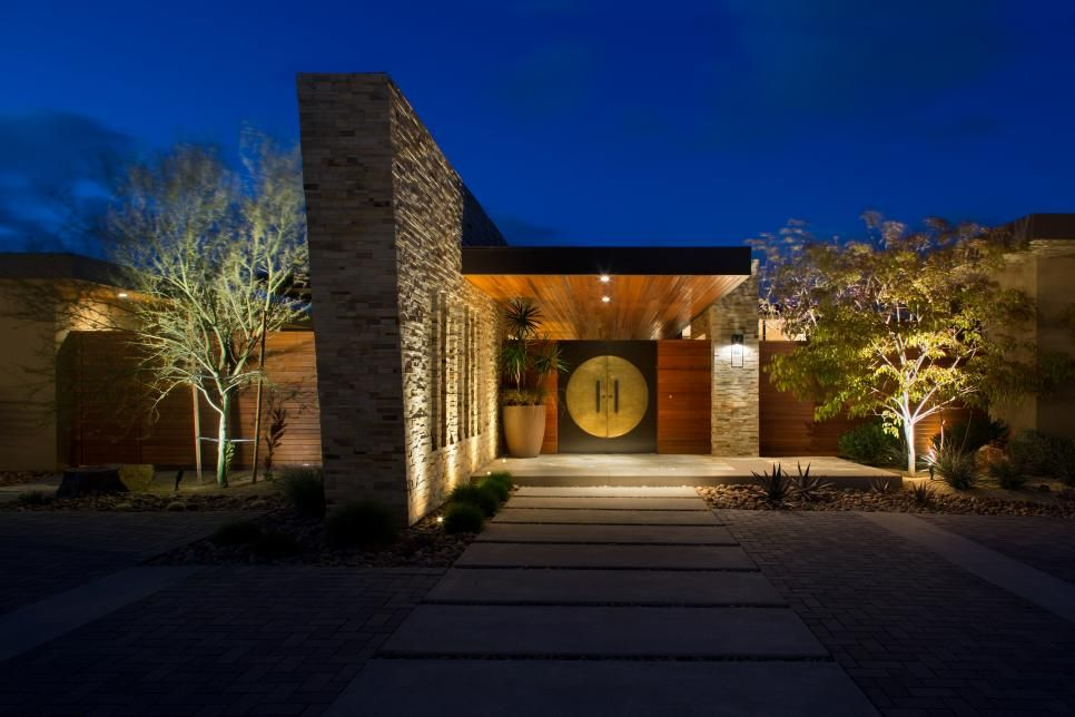 This modern home from Mark Silva features a large cantilevered overhang above Asian-inspired entry doors. The home features drought-resistant Southwestern landscaping and a blend of modern and contemporary elements indoors.