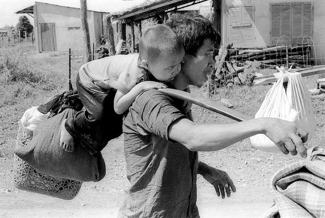 A South Vietnamese father carries his son and a bag of household possessions as he leaves his village near Trang Bom on Route 1 northwest of Saigon April 23, 1975. The area was becoming politically and militarily unstable as communist forces advanced, just days before the fall of Saigon. (AP Photo/KY Mhan)
