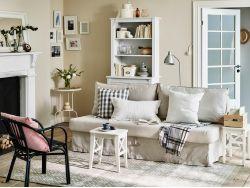 Soggiorno con divano letto beige due sgabelli bianchi usati come