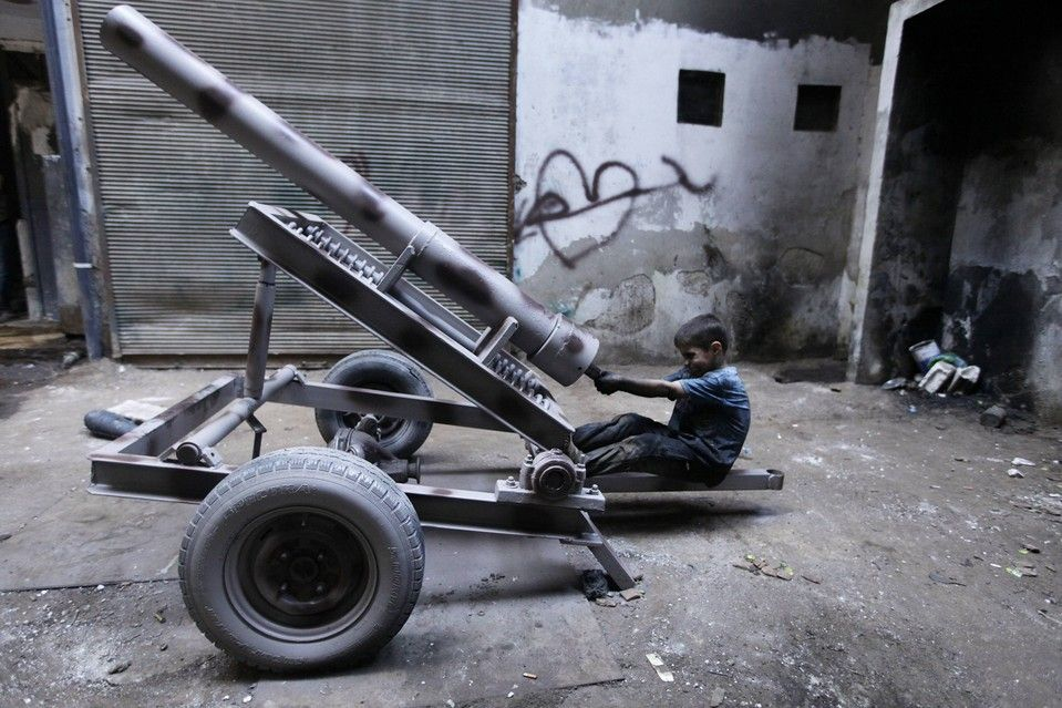 PLAYING SOLDIER: Issa, 10 years old, fixed a mortar launcher at a weapons factory used by the Free Syrian Army in Aleppo, Syria, Saturday. I...