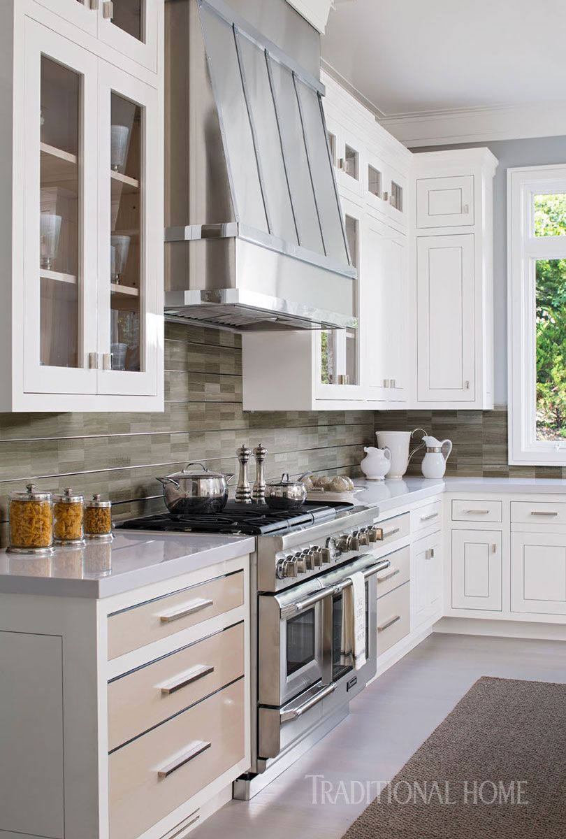 A stainless steel range sits beneath a custom hood crafted of brushed steel and polished nickel photo john bessler design robert bakes and paul kropp