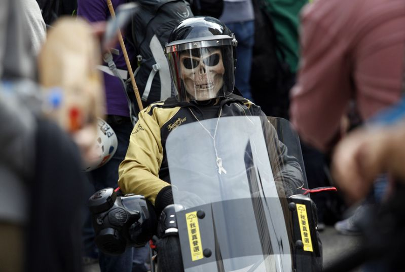 A protester in a skull mask and riot gear sits in a chair at the main pro-democracy protest site in the Admiralty district of Hong Kong.  Bailiffs on December 11 dismantled barricades at Hong Kong's main protest site after more than two months of pro-democracy rallies that demonstrators say have redefined the city's vexed relationship with Beijing.