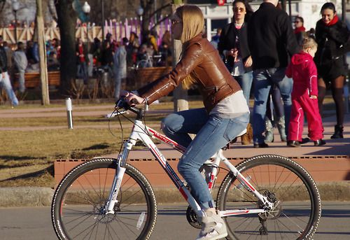 Girl On A Bicycle In A Brown Leather Jacket