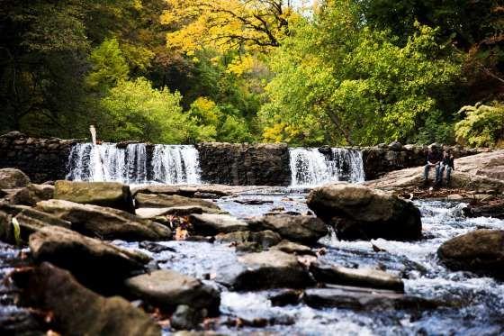 Una pareja sentada junto a una presa entre el follaje otoñal, el 16 de octubre en el Wissahickon Val... - AP Photo/Matt Rourke