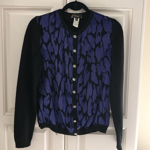 Versace black and purple cardigan This is a beautiful black cardigan from Versace. The knit part of the cardigan is 100% wool where as the detailing on the front is 77% the viscose rayon and 23% silk. The detailing on the front is slightly sheer making the cardigan sexy in true Versace fashion. There are silver buttons with DG initial initials. Shoulder to shoulder is 15 inches, length sleeve is 25 inches, armpit to armpit is 20 inches in total length is 23 inches. Versace Sweaters Cardigans