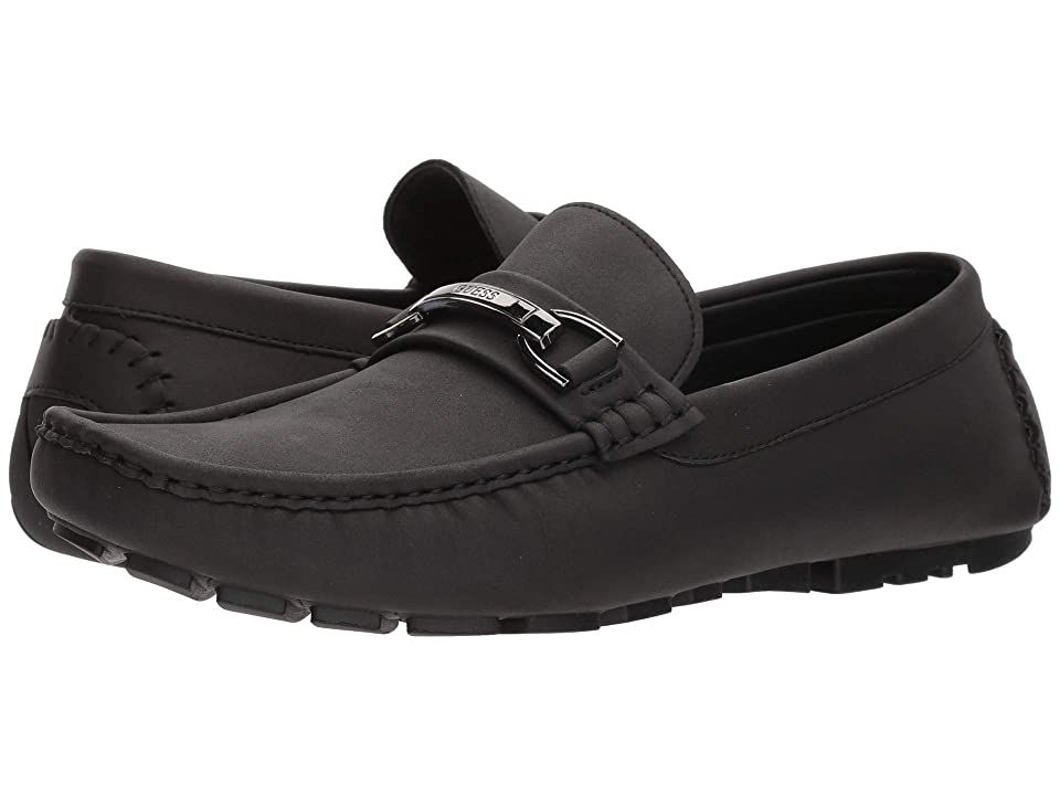 GUESS Axle (Black) Men's Shoes. Switch to the cursing lane with the GUESS Axle driver moc. Faux-leather upper. Slip-on construction. Moc-toe design with decorative hardware on vamp. Synthetic lining. Lightly padded footbed. Man-made outsole. Imported. Measurements: Weight: 10 oz Product measurements were taken using size 11  width M. Please note that measurements may vary by size. Weight of footwear is based on a single item   #GUESS #Shoes #ClosedFootwear #GeneralClosedFootwear #Black