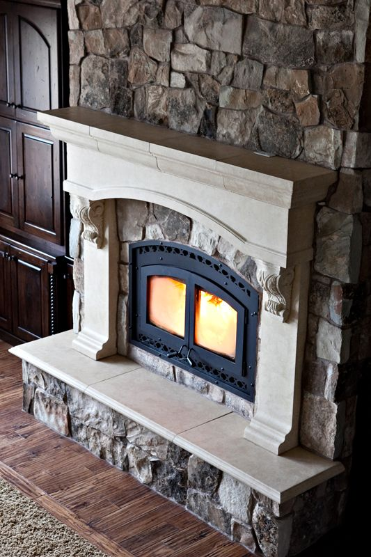 Custom cast stone fireplace mantel on stone wall