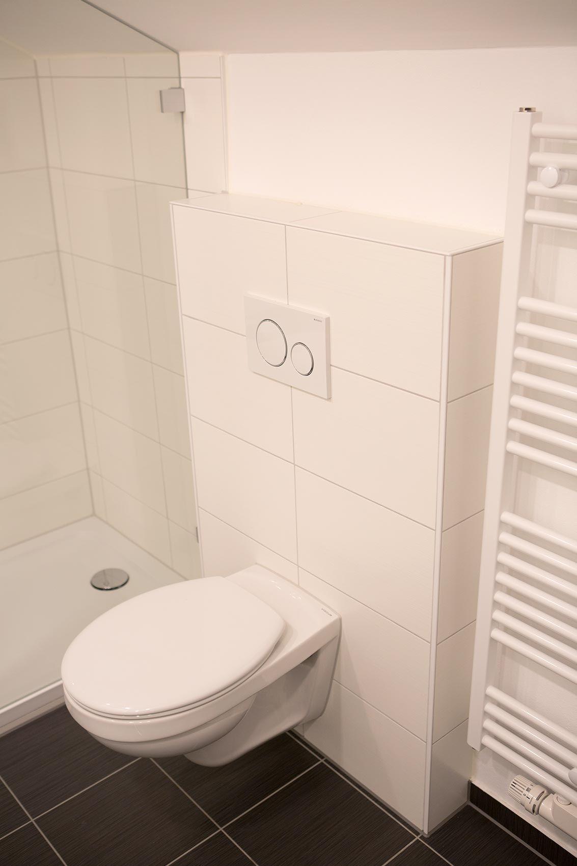 wandhängendes wc vor weiß gefliester vormauerung, fußboden mit