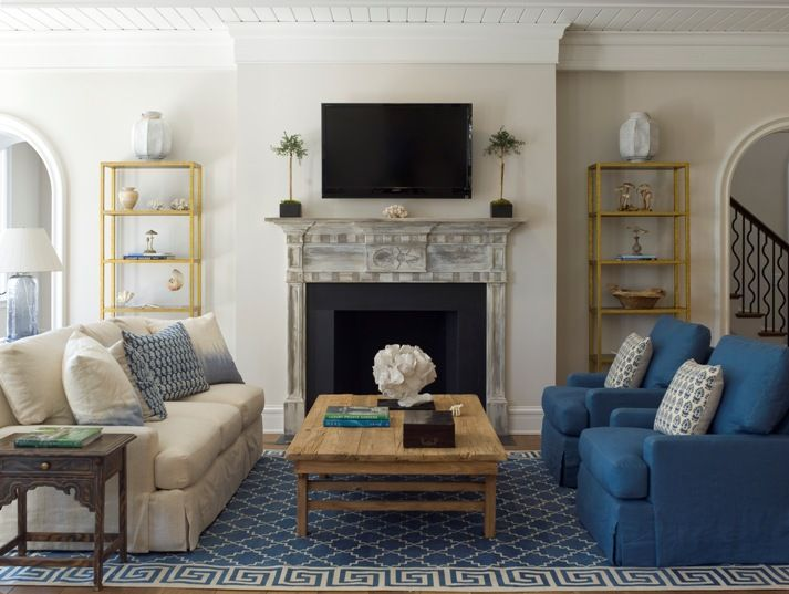 In a mirror arrangement such as this, it's unusual to see sofa and armchairs in such opposing solid colors. The rug in both colors unites them. Design by James Michael Howard.