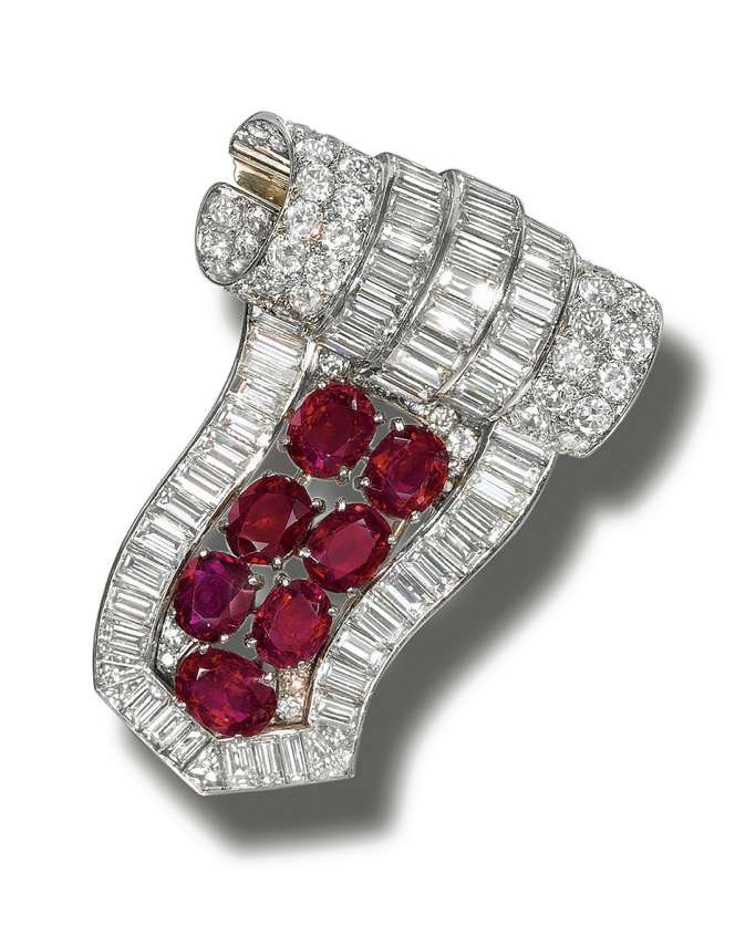 RUBY AND DIAMOND BROOCH,  CIRCA 1935.  Designed as a stylised scroll set with baguette and circular-cut diamonds and oval rubies, mounted in platinum,
