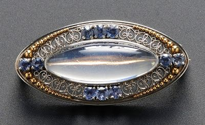 A TIFFANY 1915,s montana sapphire and moonstone brooch This delicate brooch signed by Tiffany was designed by Louis Comfort Tiffany in the beginning of the twentieth century. It is a great example of his work in platinum set with a central oval cabochon moonstone surrounded by ten Montana sapphires